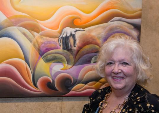 """Martha Laroche sonríe al lado de su trabajo """"Olas pasionales"""", óleo."""