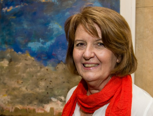 """Graciela Prioli sonríe junto a su obra: """"Lo que quedó de la ciudad""""."""