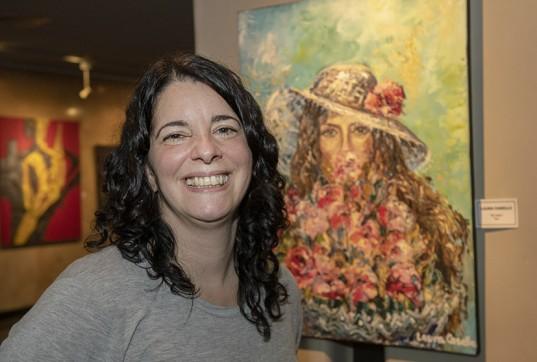 """Laura Casella sonríe junto a su obra: """"El ramo"""", óleo."""